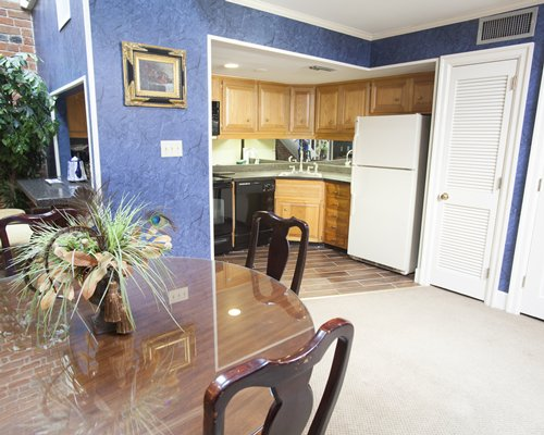 An open plan dining and kitchen area with a refrigerator.