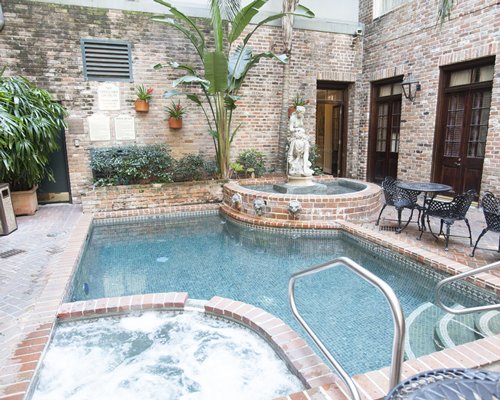 An outdoor swimming pool with hot tub fountain and patio furniture.