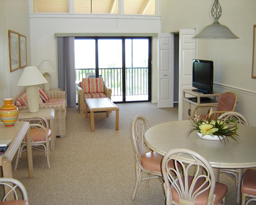A living room with open plan dining area television and balcony.