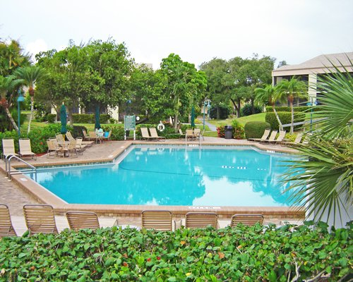 Scenic exterior view of outdoor swimming pool with chaise lounge chairs.