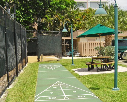 Outdoor recreation area with patio chairs sunshade and shuffleboards.