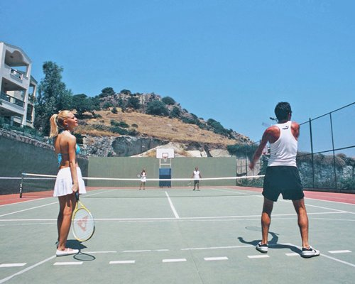 People playing in an outdoor tennis court.