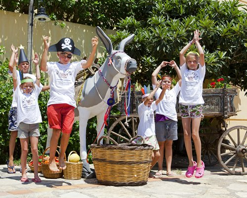 Children posing as pirates alongside a life sized statue of a donkey.