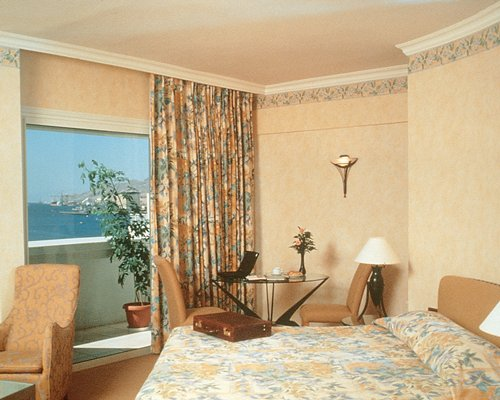 A well furnished bedroom with balcony and a view of the Gulf of Aqaba.