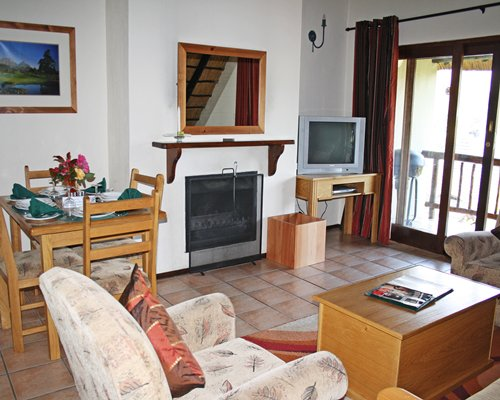 A well furnished living room with dining area fireplace and balcony.