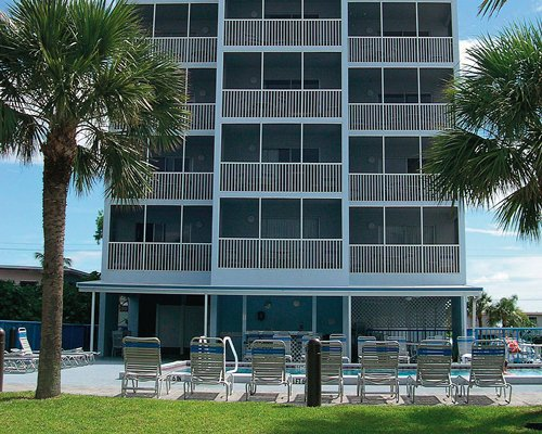 Scenic exterior view of multiple unit balconies at Beach Club I with swimming pool and chaise lounge chairs.