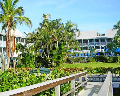 Scenic exterior view of wooden pathway to Surfrider Beach Club with multiple unit balconies.