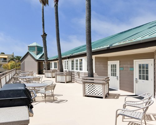 An outdoor dining area with barbecue grill alongside resort condo.