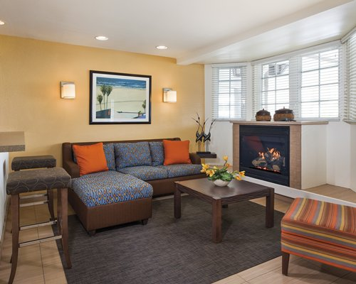A well furnished living room with a fire in the fireplace.