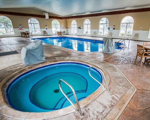 An indoor swimming pool with hot tub and patio chairs.