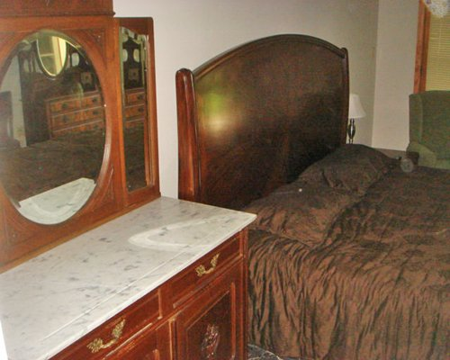 A well furnished bedroom with queen bed alongside vanity.