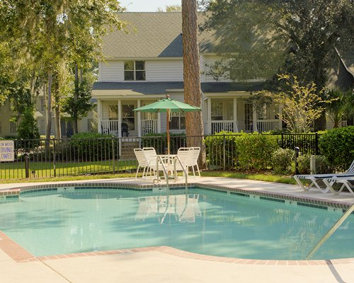 An outdoor swimming pool with patio chairs and umbrella alongside resort condo.