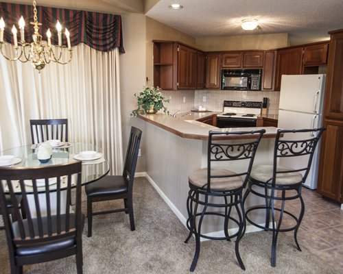 A well equipped kitchen with breakfast bar and glass top dining area.