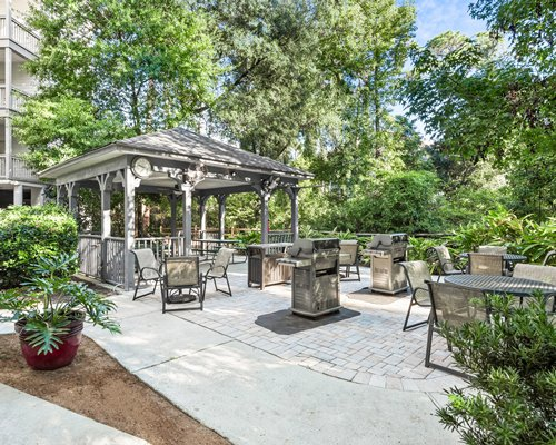 Outdoor picnic area alongside kids playground surrounded by wooded area.