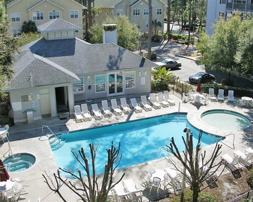 An aerial view of the outdoor swimming pool and hot tub with chaise lounge chairs.
