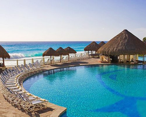 An outdoor swimming pool with chaise lounge chairs and thatched sunshades alongside the beach.