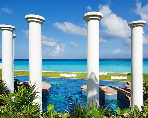 An outdoor swimming pool with pillars alongside the ocean.