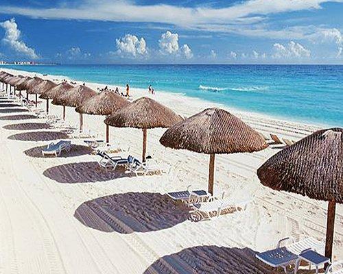 Chaise lounge chairs and thatched sunshades on the beach.