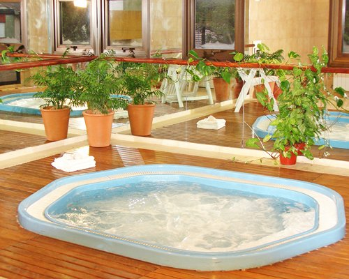 An indoor hot tub with chaise lounge chair.