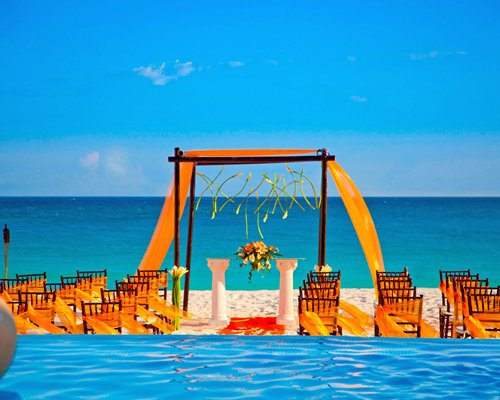 A view of beach wedding set up alongside the ocean.