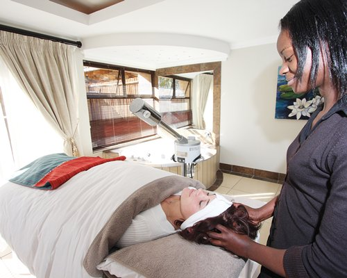 A woman enjoying the head massage in a spa.