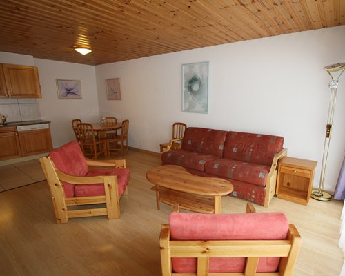 A well furnished living room with loveseat and dining area.