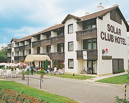 Scenic exterior view of Solar Club Hotel with outdoor restaurant.