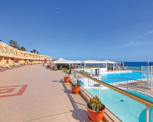 Outdoor swimming pool with sunshades alongside the ocean.