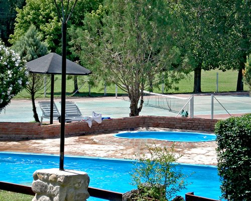An outdoor swimming pool and a hot tub with chaise lounge chairs alongside a tennis court.