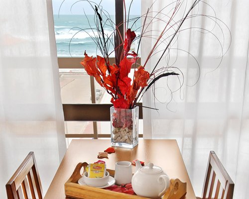 A tea set on a dining table facing the ocean.