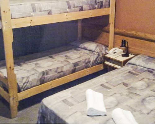 A well furnished bedroom with a bunk bed and a double bed.