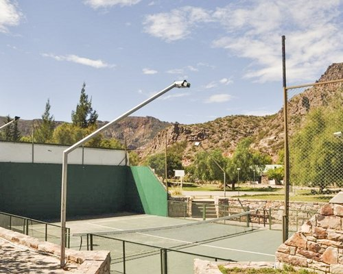 An outdoor tennis court surrounded by mountains.
