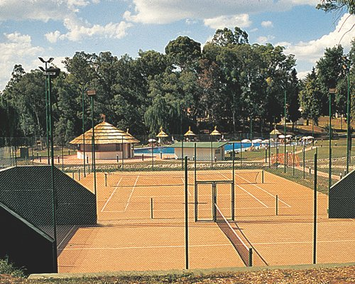 An outdoor tennis court alongside swimming pool and a poolside bar.
