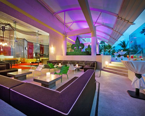 A well furnished lounge area with neon lights.