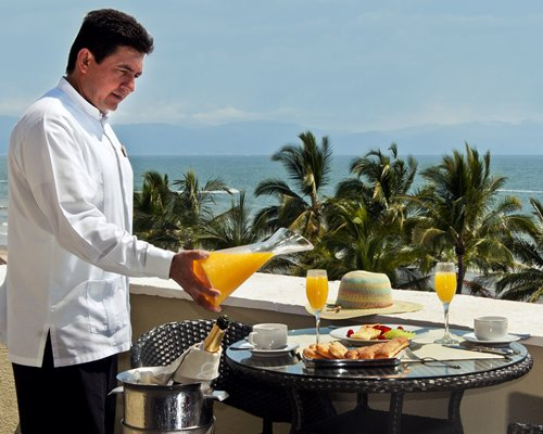 A waiter serving a drink on a terrace with ocean view.