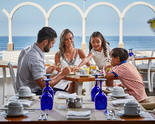 A family dining outside at a table with ocean view.