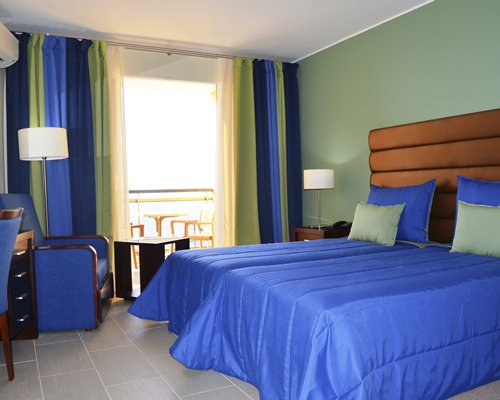 A well furnished bedroom with a twin bed and balcony view.