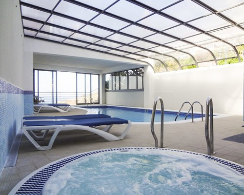 An indoor hot tub and swimming pool with chaise lounge chairs and an outside view.
