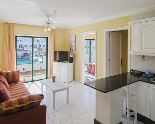A well furnished living room with open plan kitchen television and patio.
