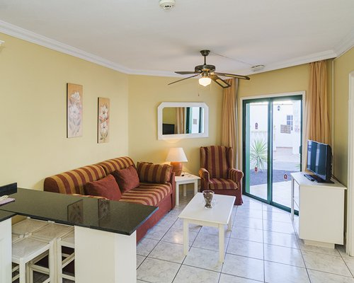 A well furnished living room with television breakfast bar and outdoor view.
