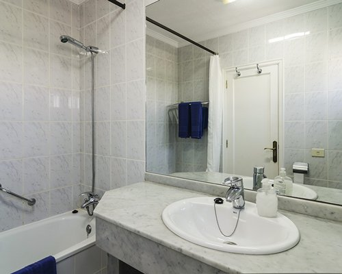 A bathroom with shower bathtub and sink vanity.