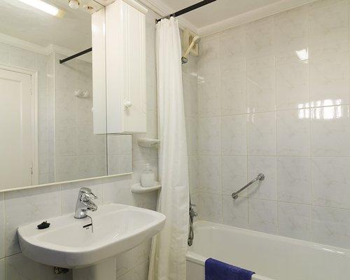 A bathroom with a single sink vanity and a bath tub.
