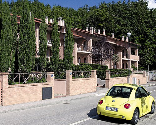 A street view of the Carpediem Assisi Living Club alongside a Volkswagen Beetle.