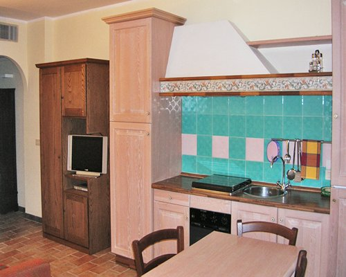 A well equipped kitchen with dining area and a television.