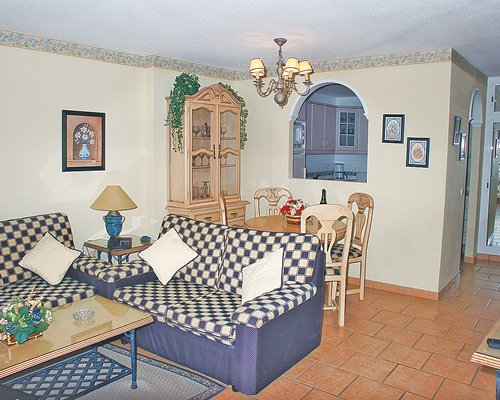 A well furnished living room with an open plan dining area and view of kitchen.