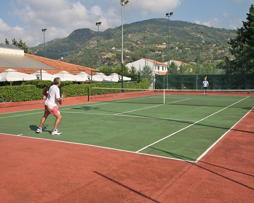 Two people playing in an outdoor tennis court.