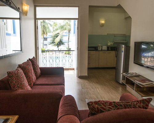 A well furnished living room with a television alongside a kitchen and an outside view.