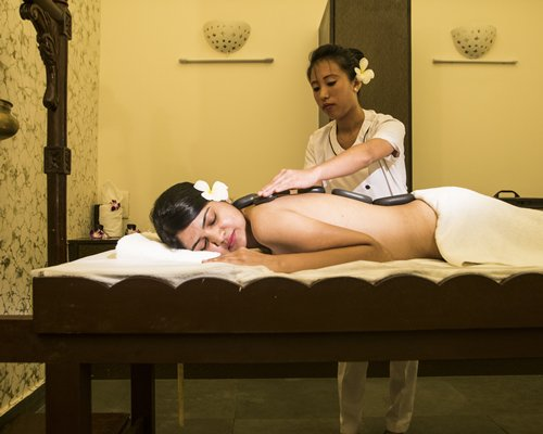 A woman enjoying body massage at a spa.