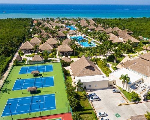 An aerial view of the resort with tennis courts pools and ocean.