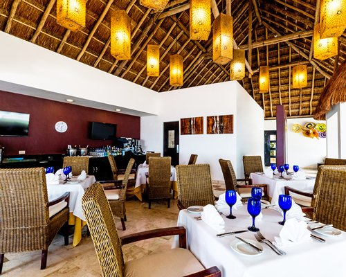 A restaurant interior with multiple dining tables bar and high thatched ceiling.
